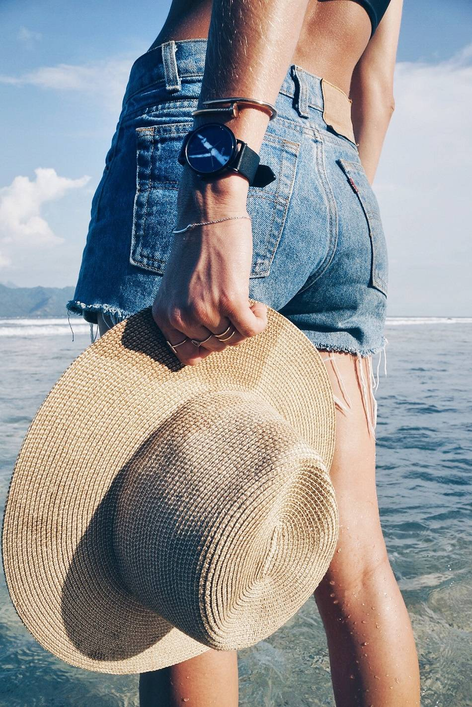 straw hat and vintage levi's shorts on beach with cluse marble watch