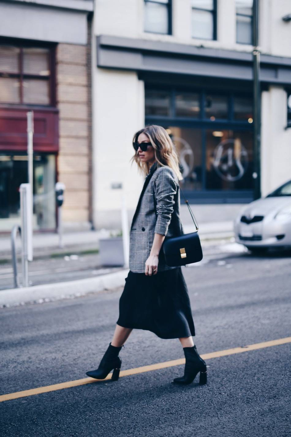 Style and beauty blogger Jill Lansky of The August Diaries in perfect black slip dress, H&M plaid boyfriend blazer, Celine bag