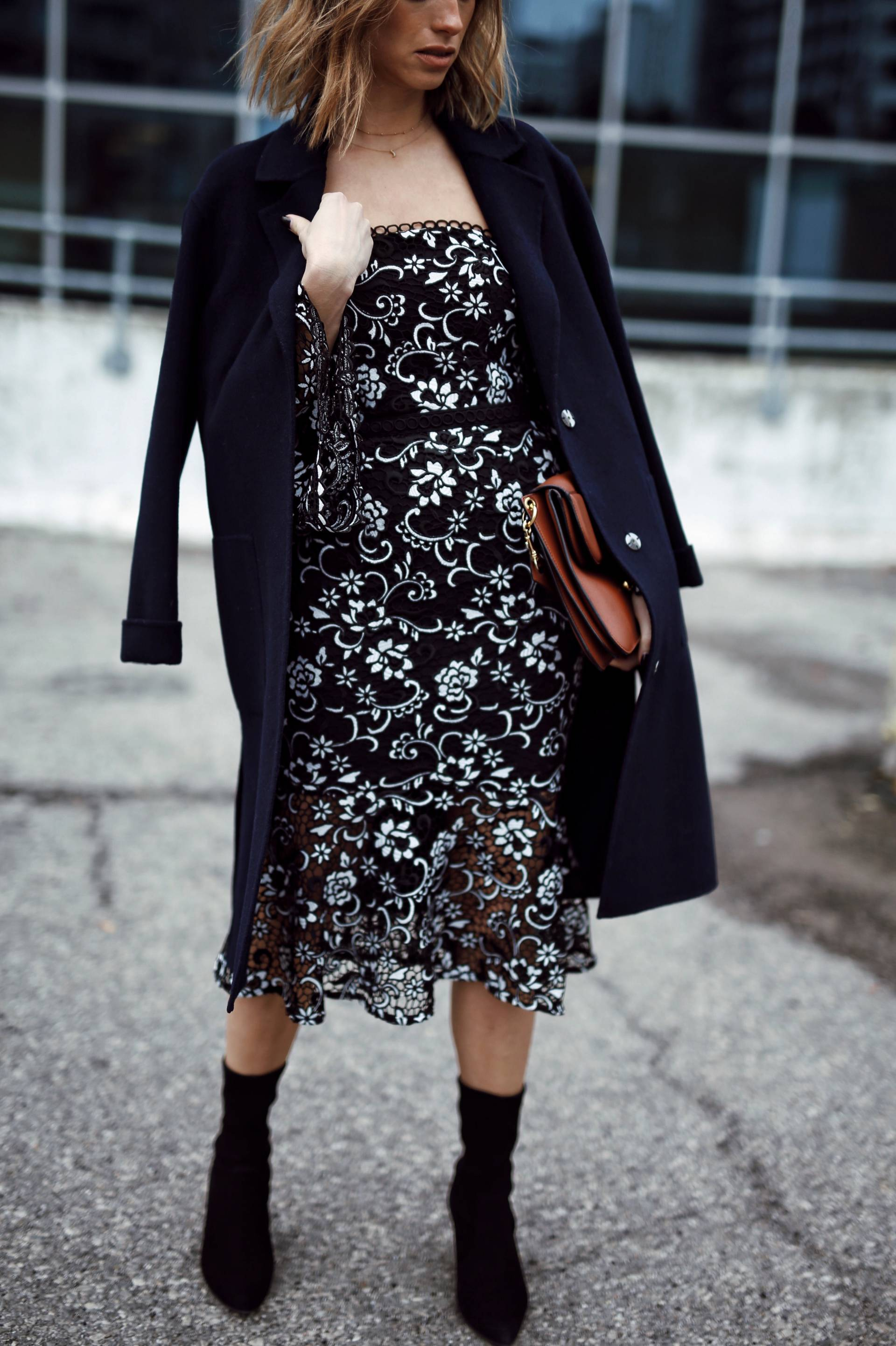 Style and beauty blogger Jill Lansky of the August Diaries in self portrait floral dress, navy coat over shoulders, stuart weitzman clinger booties