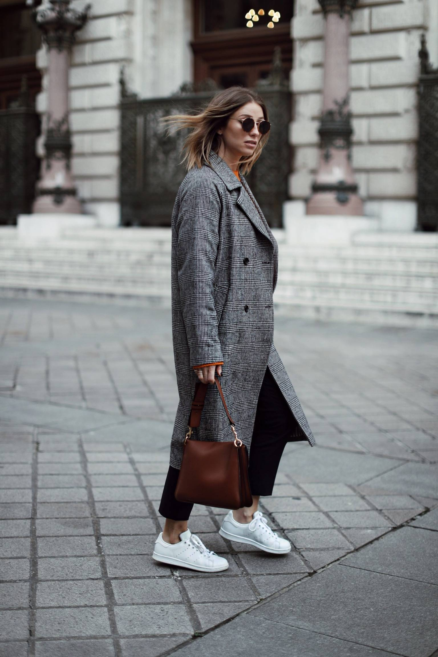 Style and beauty blogger Jill Lansky of The August Diaries on what to wear when traveling in plaid coat, sneakers, acne sweater