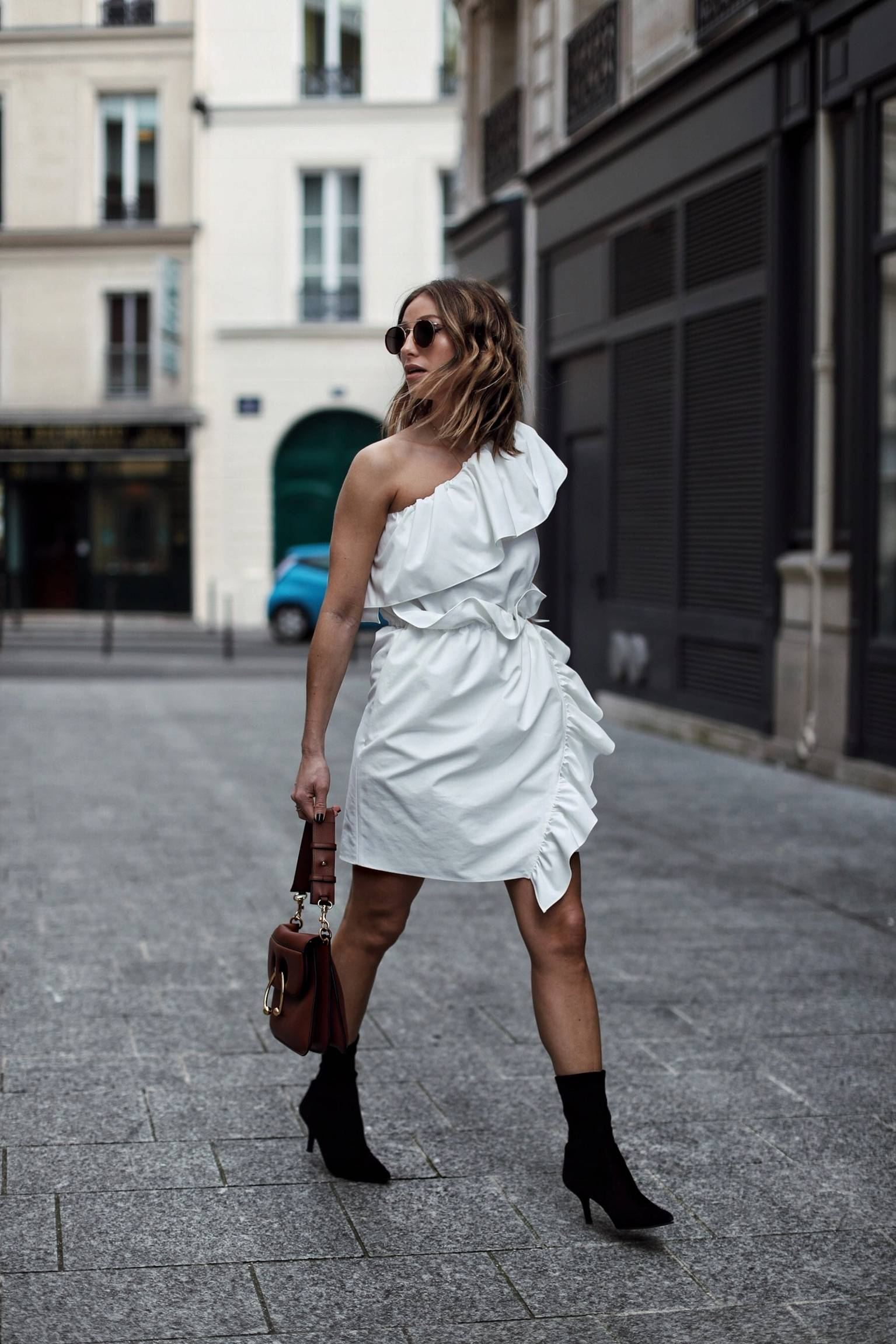 Style and beauty blogger Jill Lansky of The August Diaries in white one shoulder dress, Stuart Weitzman cling boots, JW Anderson bag, Illesteva sunglasses